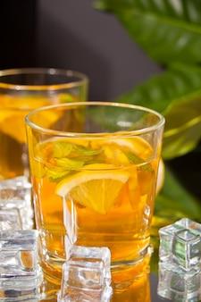 Dwie szklanki zimnej herbaty z lodem i cytryną.