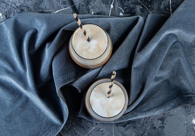 Dwie szklanki zimnej kawy z mlekiem na marmurowej powierzchni.