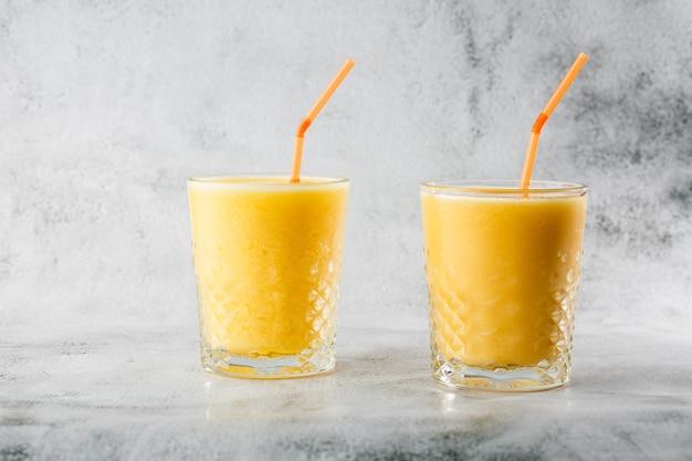 Dwie szklanki żółtych bananów, pomarańczy, koktajli mango lub soku z owoców na jasnym tle marmuru. widok z góry, kopia przestrzeń. reklama menu kawiarni. poziome zdjęcie.