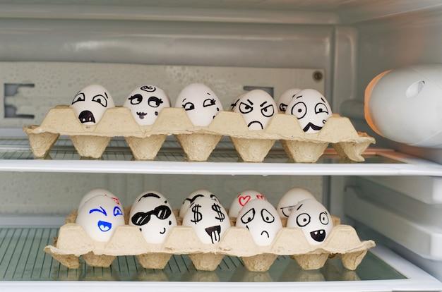 Dwie tace z malowanymi uśmiechami na jajach na półkach lodówki