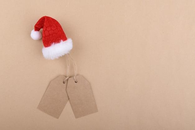 Dwie tagi z papieru siarczanowego z recyklingu zwisające z liny z kapeluszem mikołaja na papierze siarczanowym. leżał na płasko