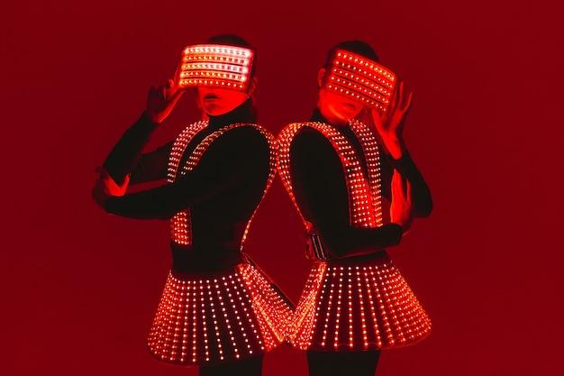 Dwie tancerki disco poruszają się w kostiumach uv.