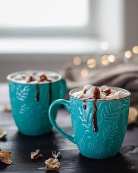 Dwie turkusowe ceramiczne filiżanki gorącej czekolady z piankami na ciemnym drewnianym stole