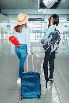 Dwie turyści z bagażem zaczynają podróżować na lotnisku. pasażerowie z bagażem w terminalu lotniczym