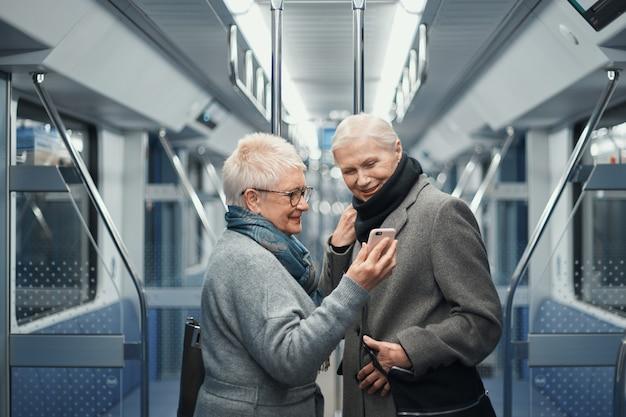 Dwie turystki komunikujące się przez łącze wideo podczas jazdy metrem