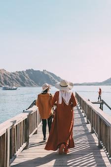 Dwie turystki spacerujące po drewnianym moście otoczonym morzem