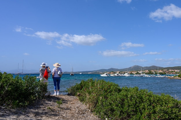 Dwie turystki w kapeluszach widok z tyłu stoją na brzegu i patrzą na morze w tle