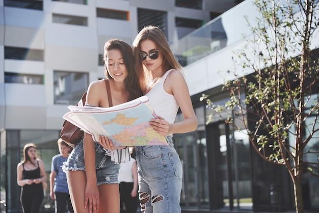 Dwie turystki z mapą odwiedzające nowe miasto i szukające drogi do hotelu.