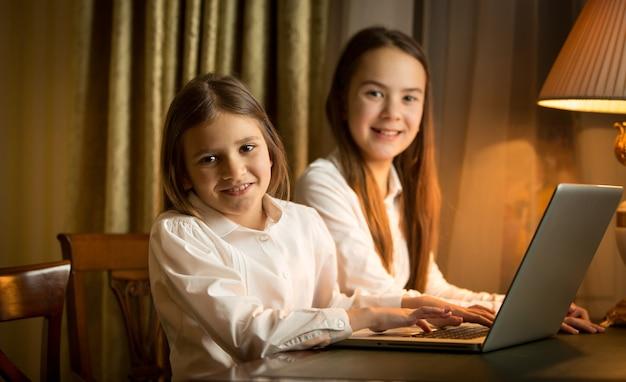 Dwie uczennice odrabiają lekcje przy laptopie w nocy