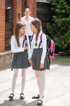 Dwie uczennice rozmawiają, idąc z domu do szkoły