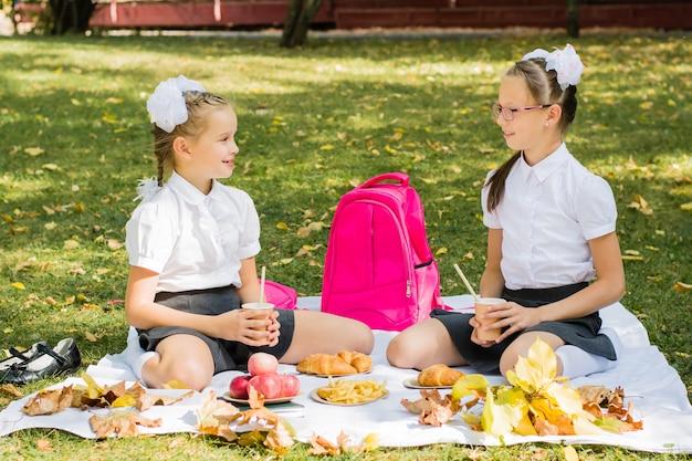 Dwie uczennice urządzają piknik na kocu w słonecznym jesiennym parku. edukacja na świeżym powietrzu dla dzieci. powrót do koncepcji szkoły