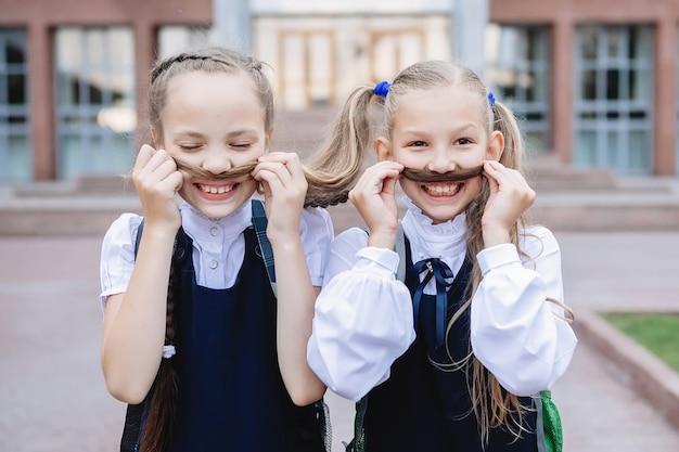 Dwie uczennice w mundurkach bawią się, robią wąsy z warkoczy.