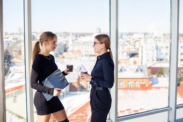Dwie udane menedżerki rozmawiają o wspólnym projekcie, stojąc przy oknie w biurze. młode ekonomistki, ubrane w formalne stroje, rozmawiają w przerwach i piją kawę.