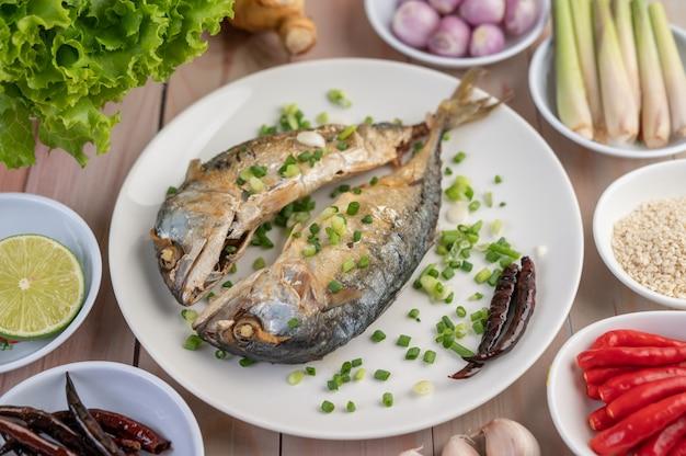 Dwie ugotowane makrele, umieszczone w białym naczyniu, posypane szczypiorkiem.