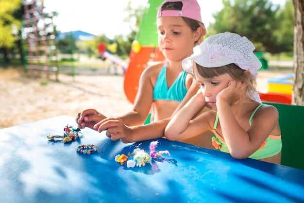 Dwie urocze dziewczynki bawiące się lalkami na świeżym powietrzu, relaksując się na plaży w upalny letni dzień. koncepcja aktywnych gier dla dzieci.