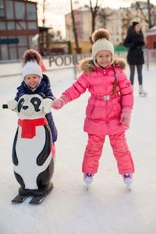 Dwie urocze dziewczynki jeżdżące na łyżwach na lodowisku