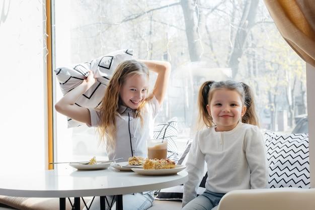 Dwie urocze dziewczynki siedzą w kawiarni i bawią się w słoneczny dzień. rekreacja i styl życia.