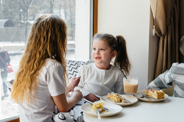 Dwie urocze dziewczynki siedzą w kawiarni i bawią się w słoneczny dzień