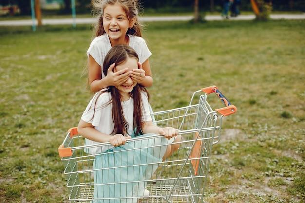 Dwie urocze dziewczynki w białych koszulkach i niebieskich spódnicach grają w letnim parku