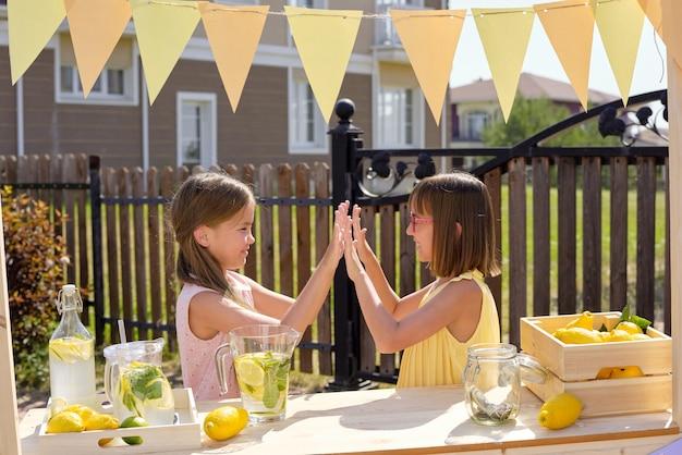 Dwie urocze dziewczyny bawiące się w gorący letni dzień, stojąc przy drewnianym straganie ze świeżymi cytrynami i chłodną domową lemoniadą