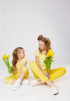 Dwie urocze dziewczyny o blond włosach z żółtymi tulipanami w żółtych ubraniach