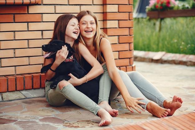 Dwie urocze dziewczyny w letnim parku z psem