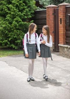 Dwie urocze dziewczyny w mundurach chodzą do szkoły i rozmawiają