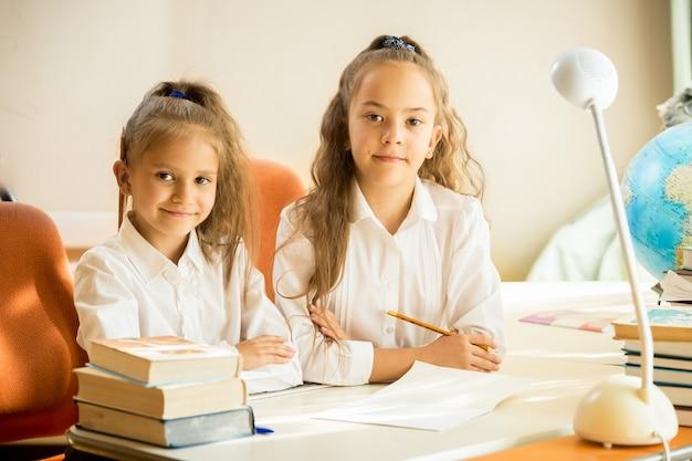Dwie urocze dziewczyny w mundurkach szkolnych siedzące przy biurku i odrabiające pracę domową