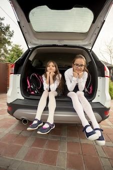 Dwie urocze dziewczyny w mundurkach szkolnych siedzące w otwartym bagażniku samochodu