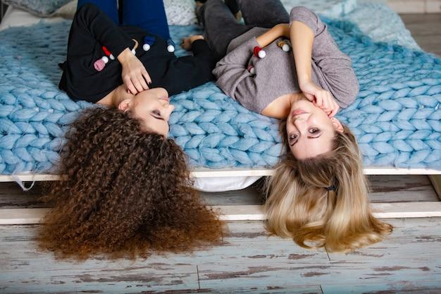 Dwie urocze dziewczyny w świątecznych swetrach i dżinsach leżą na ciepłym owinięciu głową w dół na łóżku w pokoju
