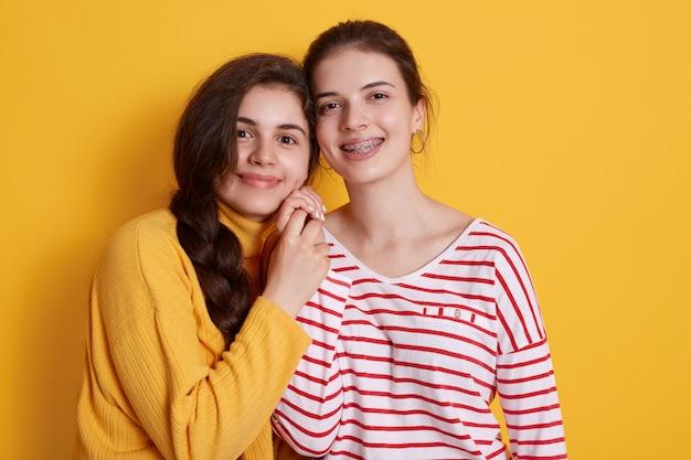 Dwie urocze dziewczyny w zwykłych strojach, wyglądające na szczęśliwe, stojące i uśmiechnięte