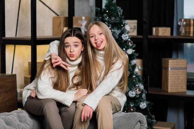 Dwie urocze dziewczyny z całowania wyrazem twarzy z choinką. długowłosa europejska dama stojąca obok drzewa i prezentów