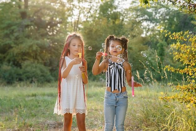 Dwie urocze dziewczyny z warkoczykami bawią się w parku, dmuchając w bańki mydlane.