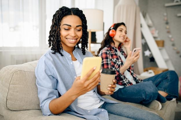 Dwie urocze kobiety w słuchawkach, słuchanie muzyki i napojów kawowych na kanapie. ładne dziewczyny w słuchawkach relaksują się w pokoju, miłośnicy dźwięku odpoczywają na kanapie, osoba korzystająca z telefonu komórkowego