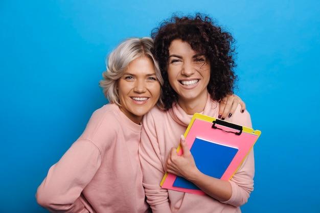 Dwie urocze młode studentki śmiejąc się i przytulając, patrząc na kamery, trzymając swoje książki do nauki na białym tle na niebieskim tle.