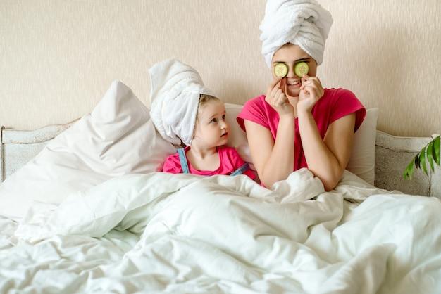 Dwie urocze siostry siedzą na łóżku w białym ręczniku i nakładają plasterki ogórka na oczy. dziewczynki mają śmieszną twarz. poranek twarzy, kosmetologia. dorosła mimika. pierwszy makijaż nastolatków.
