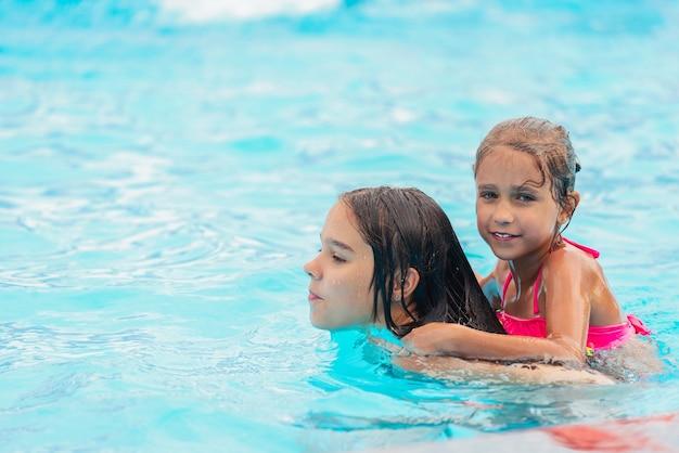 Dwie urocze siostrzyczki pływają w basenie podczas wakacji w słoneczny ciepły letni dzień
