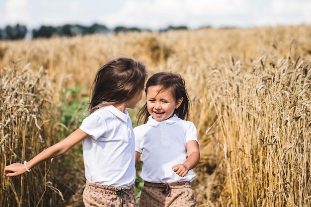 Dwie urocze siostrzyczki szczęśliwie spacerujące w polu pszenicy w ciepły i słoneczny letni dzień