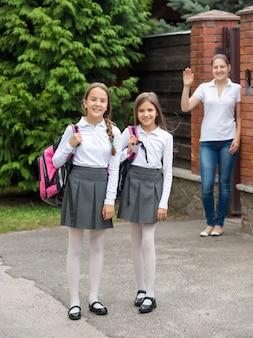 Dwie urocze uśmiechnięte dziewczyny wychodzące rano z domu do szkoły school