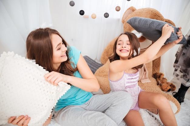 Dwie urocze wesołe siostry walczą o poduszki i bawią się w domu