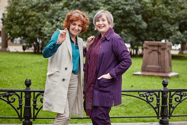 Dwie uśmiechnięte dojrzałe kobiety prowadzą wesołą rozmowę w miejskim parku w deszczu.