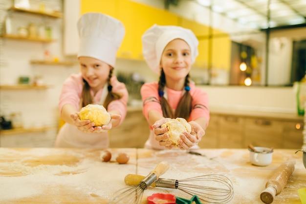 Dwie uśmiechnięte dziewczynki gotuje w czapkach pokazuje kulki ciasta