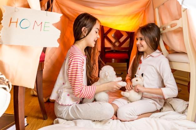 Dwie uśmiechnięte dziewczyny bawiące się w domu z kocyków w sypialni