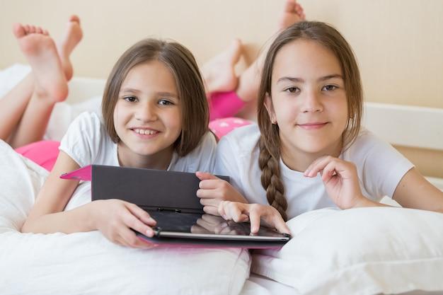 Dwie uśmiechnięte dziewczyny leżące w łóżku i korzystające z cyfrowego tabletu