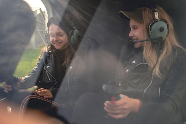 Dwie uśmiechnięte dziewczyny nastolatka w słuchawkach lotnika siedzące w kokpicie helikoptera