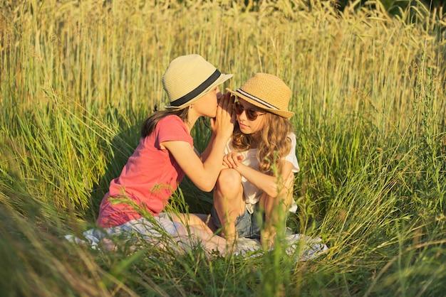 Dwie uśmiechnięte dziewczyny siedzą na trawie, dzieci mówią