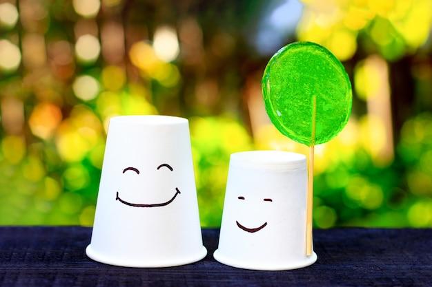 Dwie uśmiechnięte filiżanki z zielonym lizaka emocją radości symbolem przyjaźni