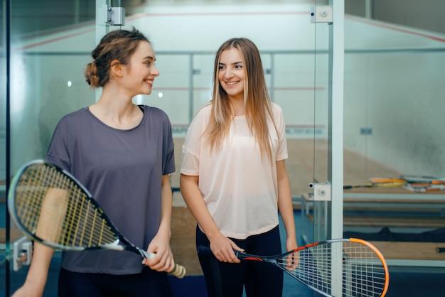 Dwie uśmiechnięte kobiece zawodniczki w squasha pozuje w szatni. młodzież na treningu, aktywne hobby sportowe, trening fitness dla zdrowego stylu życia