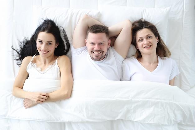 Dwie uśmiechnięte kobiety i mężczyzna leżą na łóżku