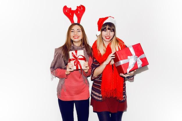 Dwie uśmiechnięte kobiety posiadające prezenty na nowy rok. noszenie uroczych kapeluszy maskaradowych. szczery uśmiech. świętowanie nastroju. portret z lampą błyskową.